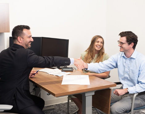 couple at desk with man shaking hands